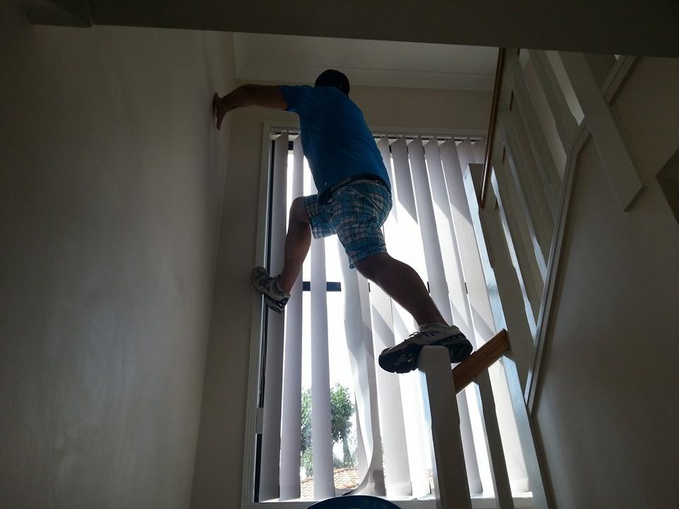 Hanging the vertical blinds back up after cleaning them.